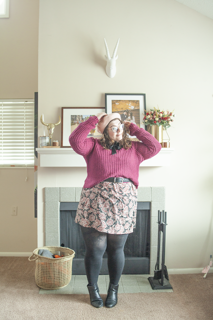 An outfit consisting of a pastel pink wool beret, a berry collared sweater layered over a black and pink paisley peter pan collar dress and black chelsea boots.