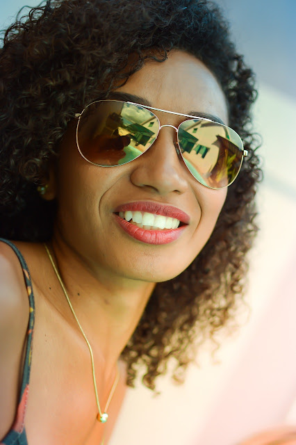 Beautiful African-American woman wearing mirror sunglasses and a minimalist gold necklace
