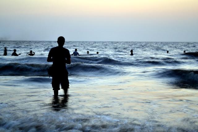Daman sea Gujarat Travel Tourism Guide India man walking into sea wet