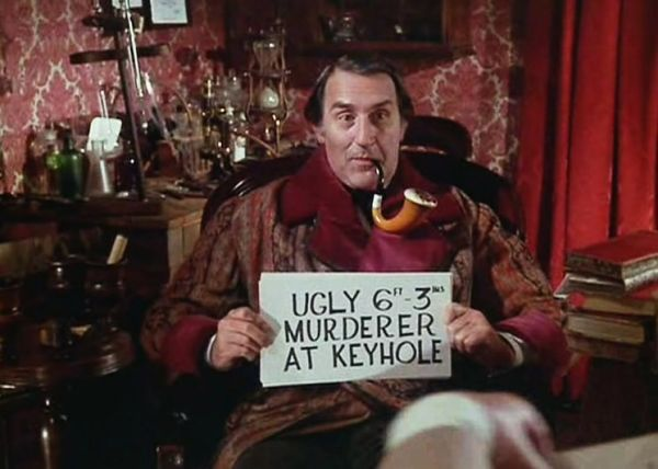 Douglas Wilmer as Sherlock Holmes holding up a hand written sign