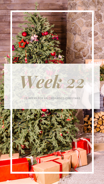 A festive scene with a Christmas tree and gifts with the text week 22 across the centre