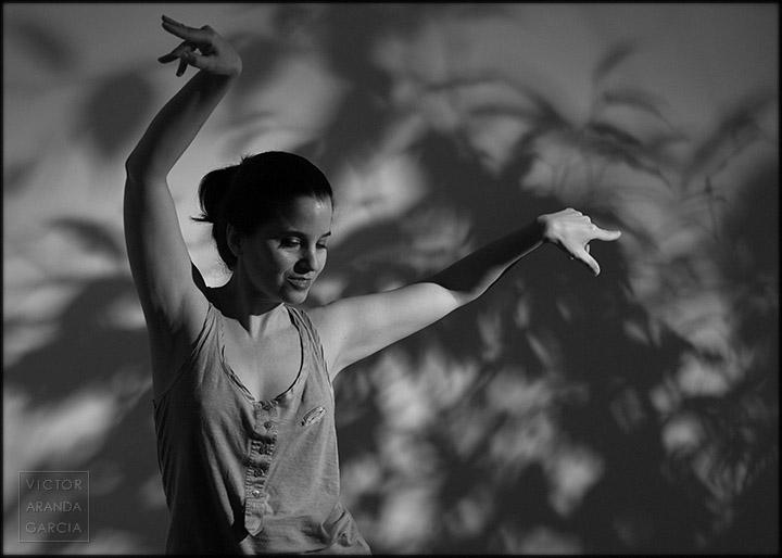 Fotografía en blanco y negro de una chica bailando con los brazos en alto y un fondo de sombras