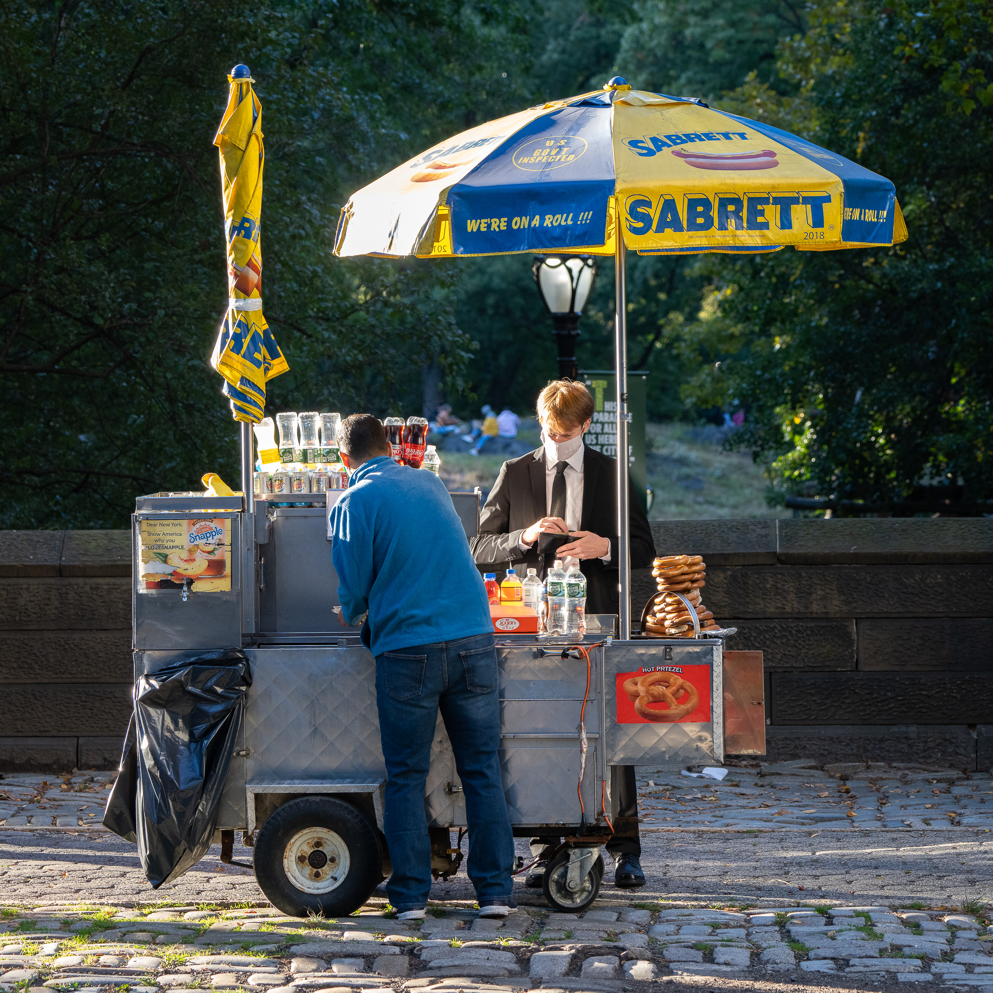 a photo of a man buying a pretzel at a stand near central park new york city