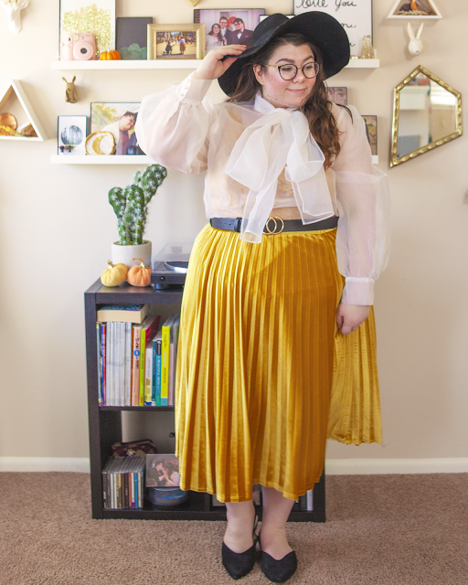 An outfit consisting of a black wide brim floppy hat, a long balloon sleeve sheer blouse with a large attached pussy bow over a mustard yellow lace tank top, tucked into a mustard yellow velvet pleated midi skirt and black pointed toe slingback flats.