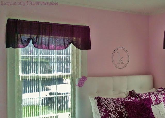 Teen girl's purple bedroom with beads on window and purple bedding