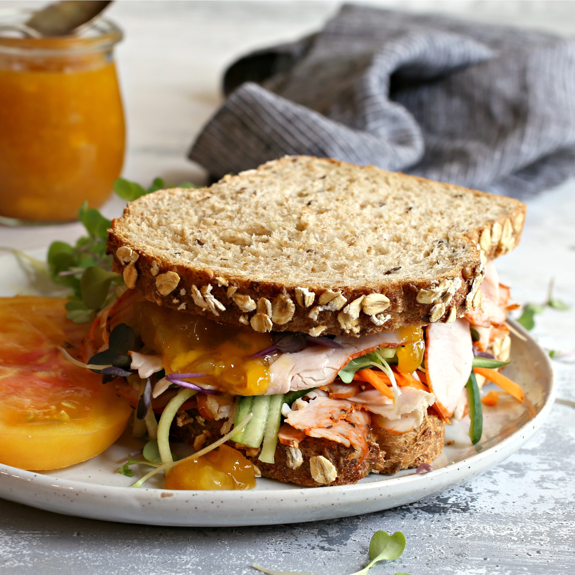 Recipe for a thick turkey and vegetable sandwich, topped with a sauce of mango, honey, lemon and spices.