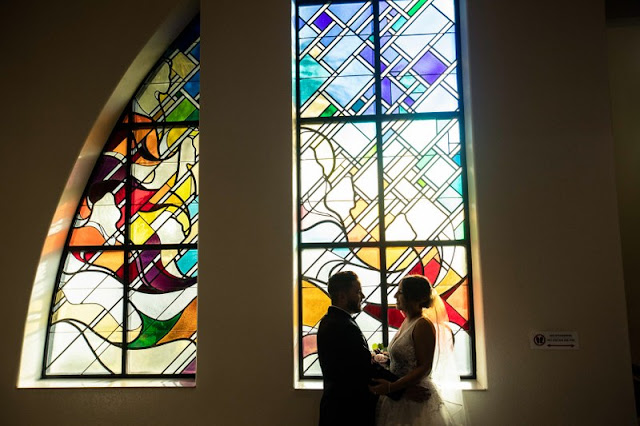 bride and groom in front of stained glass windows