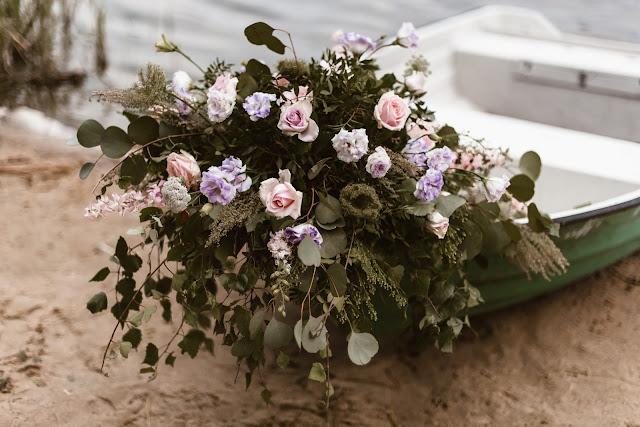 Stylizowana sesja zdjęciowa, Młoda Para w łodzi przystrojonej kwiatami, sesja zdjęciowa, romantyczny rejs, podróż poślubna, sesja ślubna, małżeństwo, talk about love, suknia ślubna, bukiet ślubny, florystyka, aranżacja kwiatowa,