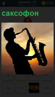 Мужчина играет на закате на саксофоне мелодию. Его силуэт хорошо видно на фоне сумерек