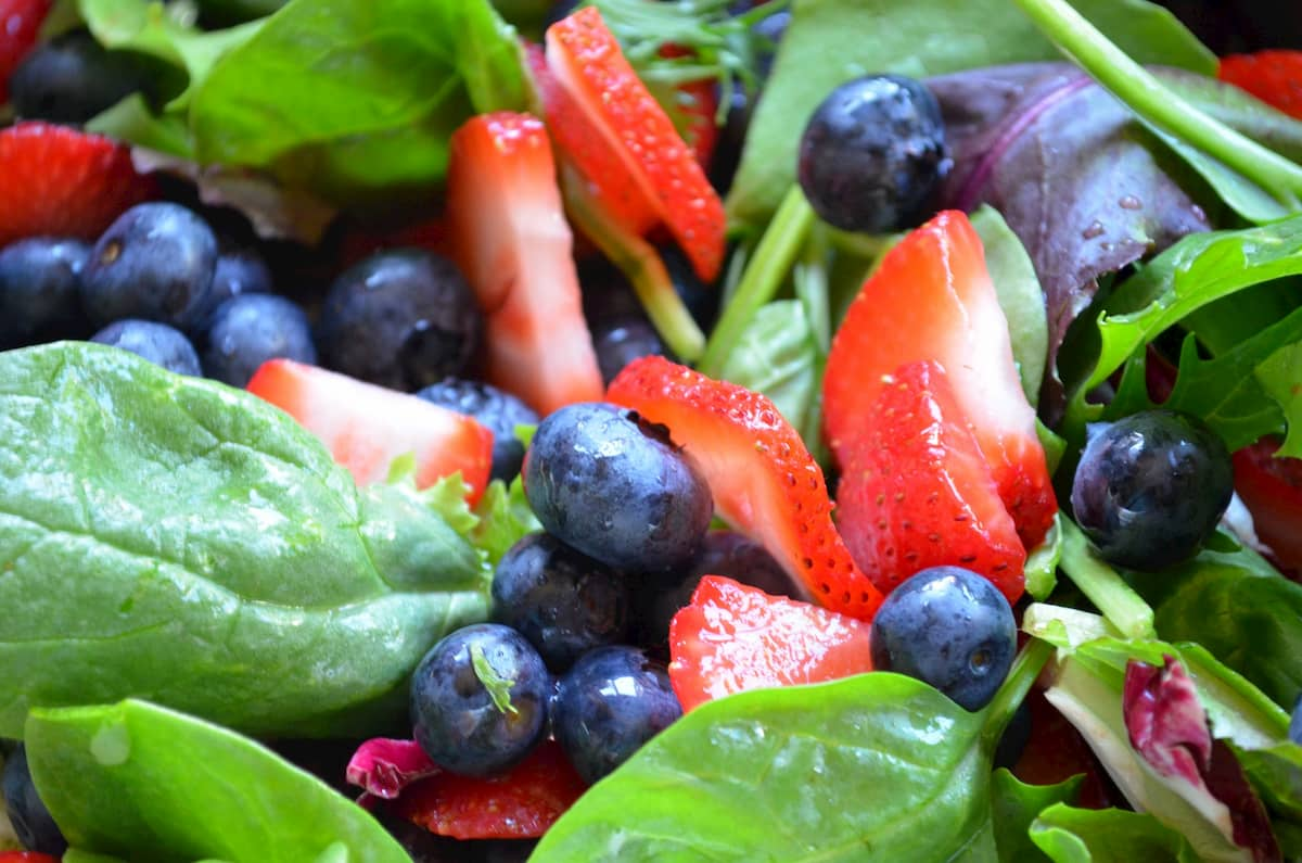 Baby Lettuce Greens topped with sliced strawberries and blueberries.