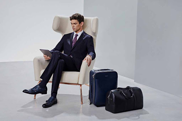A man in a black suit or jacket or coat or blazer and a black shoes siting in a chair with his legs crossed and a tablet in his hands with a bag and a suit case beside him.