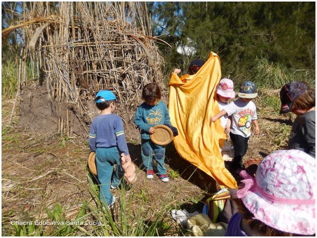 Niños jugando en la vivienda guaraní - Chacra Educativa Santa Lucía
