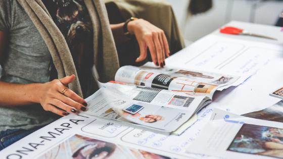 Mulher folheando revista sobre a mesa