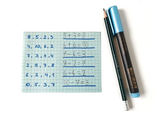 niebieska kartka, na której zapisane są po przecinku cztery liczby. Obok dziecko zapisało działania z wykorzystaniem trzech z czterech liczb. Są to działania z dodawaniem i odejmowaniem.