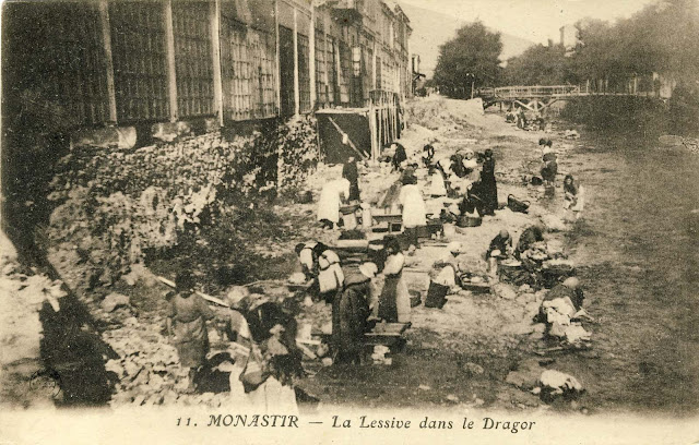 """Washerwomen in the river Dragor. In the background is seen """"Lenski"""" Most. The shops on the left were also destroyed. All bridges on Dragor river at the time were wooden."""