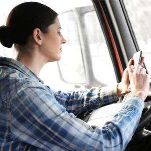 Female trucker using TruckLogics trucker mobile App for fleet management