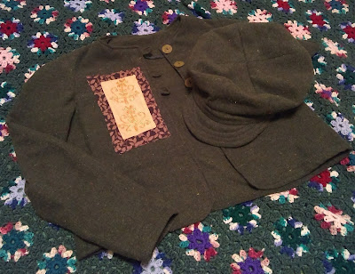 Dark-to-olive-green lightweight jacket and newsboy-style hat with brim and eight-paneled crown. The right-front of the jacket has a layered applique that consists of a rectangle of yellow fabric, decorated with yellow embroidery, inside a border of dark- and light-brown floral.