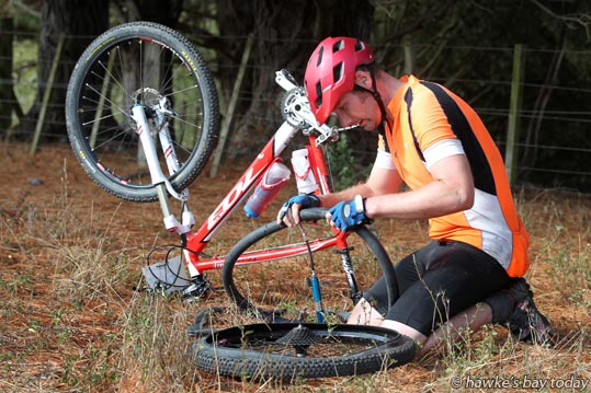 Jason Bye, Havelock North, mends his second puncture, between Kahuranaki and Te Mata Peak - Action from the Triple Peaks Challenge, a run and/or cycle event from Havelock North, over Mt Erin, Kahuranaki and Te Mata Peak, then back to Havelock North Domain. photograph