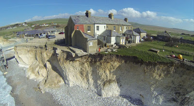 Image shows a house hanging over a cliff edge