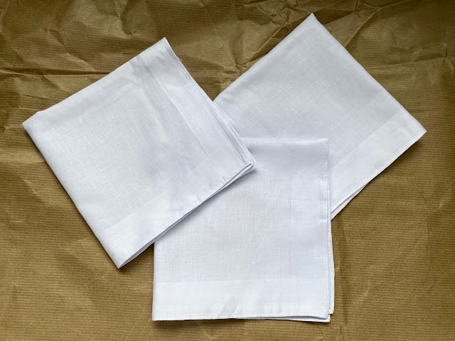3 white cotton handkerchiefs folded into squares