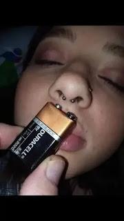 Acercando pilas de 9 voltios a piercing en la nariz
