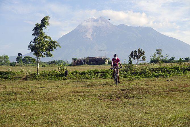 Berfoto naik sepeda berlatar belakang Gunung Merapi