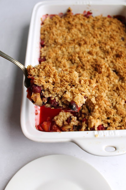 first spoonful of cranberry apple crisp being lifted out of pan