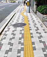 Yol kenarında büyük küçük beyaz ve gri renkli kare taşlar döşenmiş sarı çizgili tretuvar ya da kaldırım