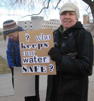 Woman with ransom note-style sign reading Who will keep our water safe?