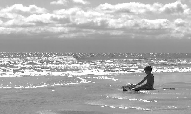 A boy enjoying the warm Atlantic waters at Huntington Beach State Park, SC. Tiny trailer camping