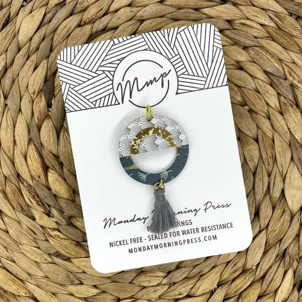patterned paper necklace pendant with tassel on display card