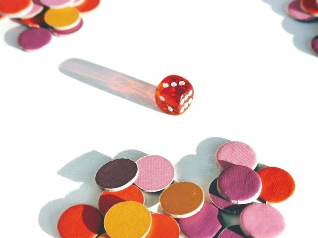 na zdjęciu widać czerwoną kostkę do gry a wokół niej leżą trzy stosy żetonów