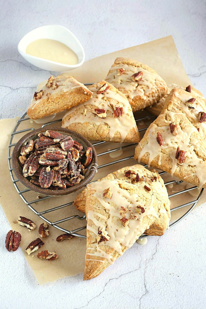 Recipe for scones baked with maple syrup and cinnamon, topped with a maple glaze and candied pecans.
