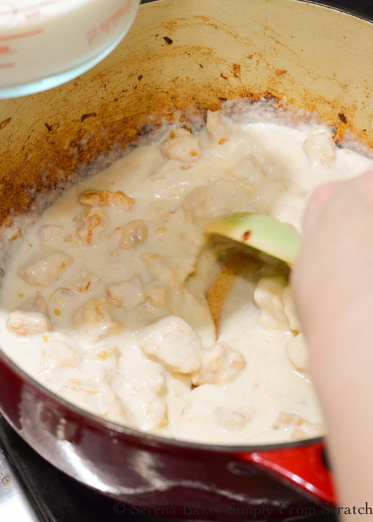 Milk being stirred in chicken and flour mixture.