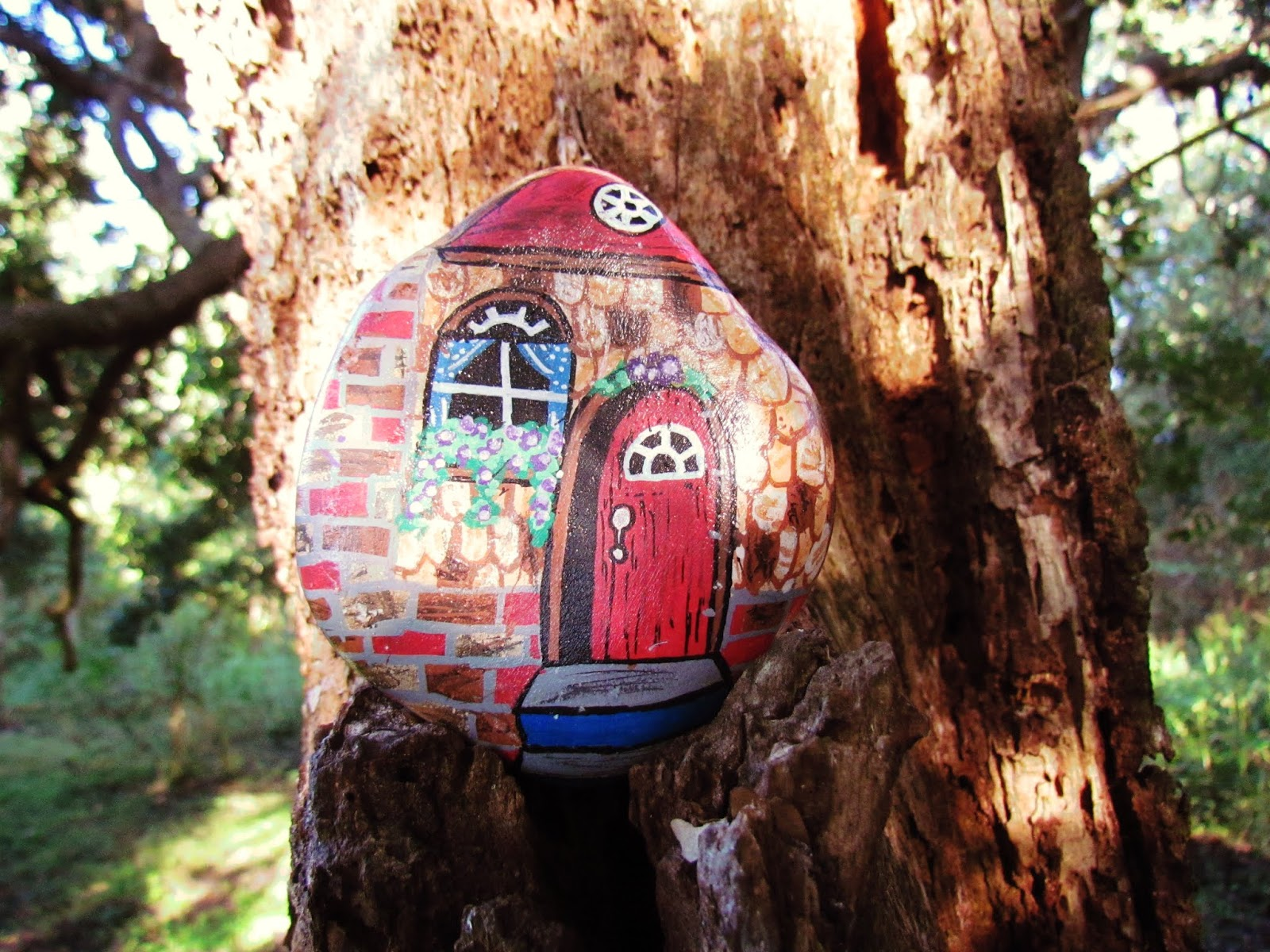 A painted rock by artist of a house cottage in the woods hoisted by a tree