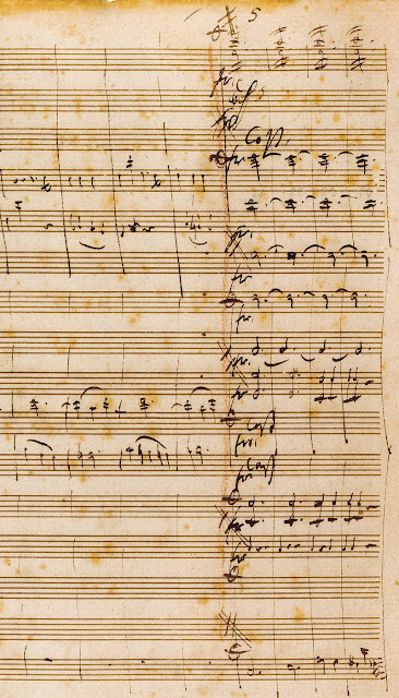 A cropped view of the third page of the autograph score of first movement of Mozart's c minor piano concerto; Mozart has marked the score to indicate that additional measures (written on a subsequent page) are to be inserted between the measures we now know as 43 and 63.