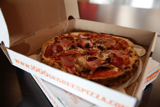 a canadian bacon pizza sits in a white cardboard box that says 1000 Degrees Pizza on the side
