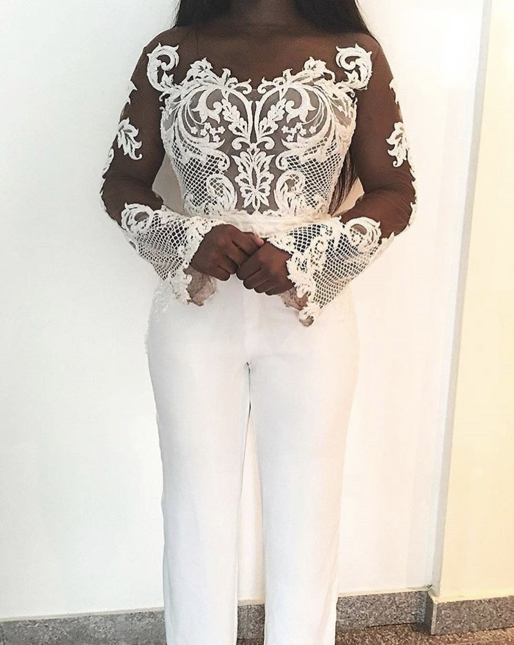 girl wearing a white lace bell sleeve bridal jumpsuit