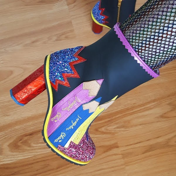 close up wearing pencil themed ankle boots in black with bright coloured applique and pencil shaped heel