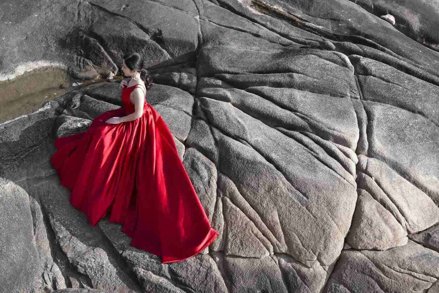 woman in red gown on rock - fair trade vs colourful fashion