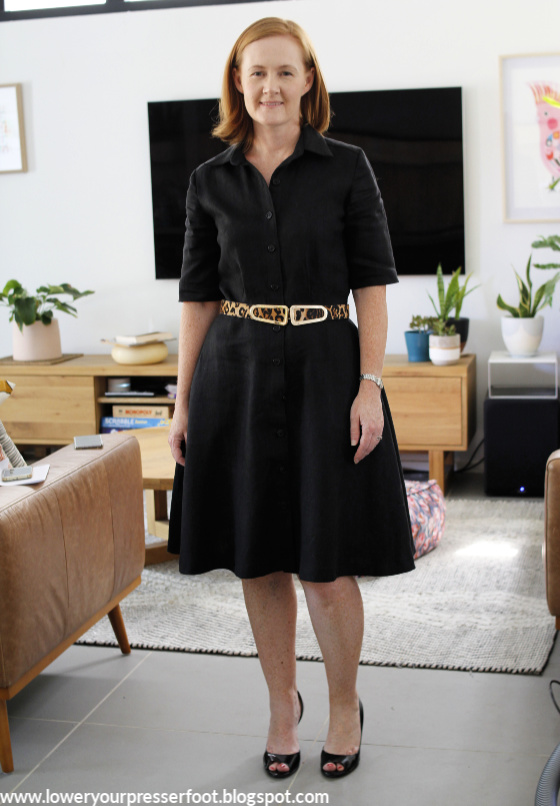 a lady posing in a black shirt dress with leopard belt in front of a lounge room