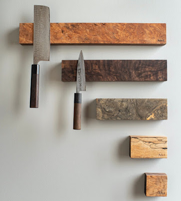 Five wall-mounted knife racks, in different woods and size. The two longest ones each have a knife hanging on them.
