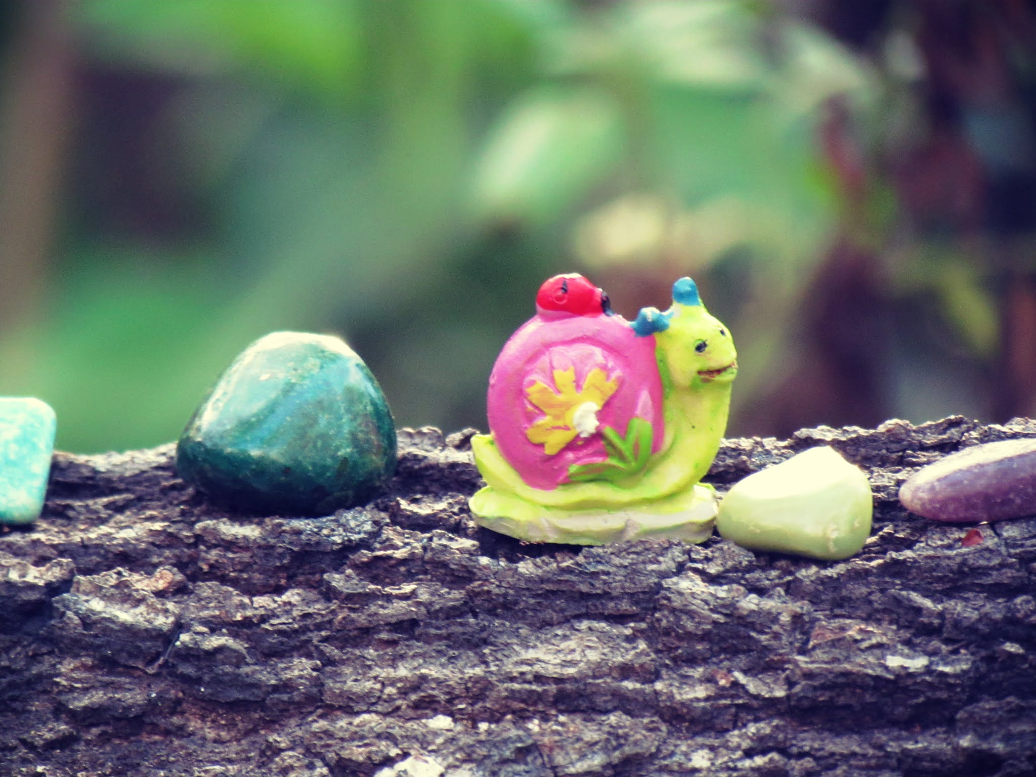 A snail toy figurine on a wooden log in an emerald green forest surrounded by healing crystals and forage mushrooms