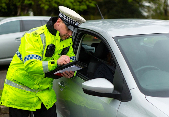 Image: Hertfordshire police officer writing out a speeding ticket Image courtesy of Hertfordshire Constabulary