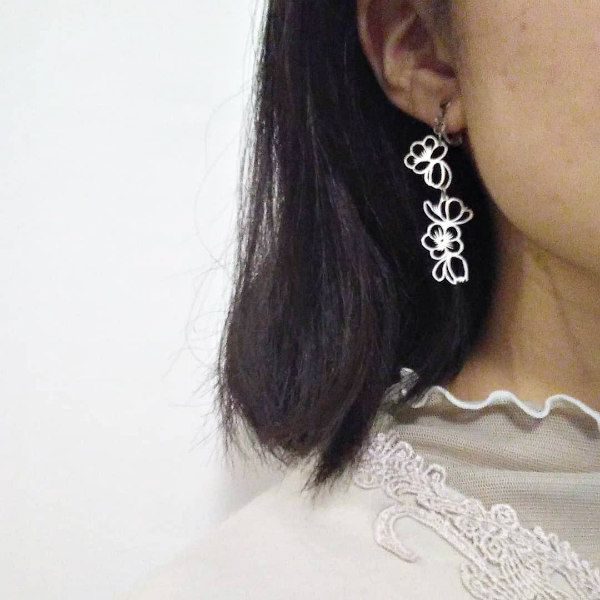 white paper cut floral clip earring on model