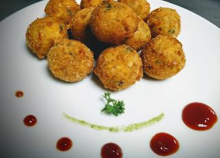 Garnished Corn cheese balls serving with sauce