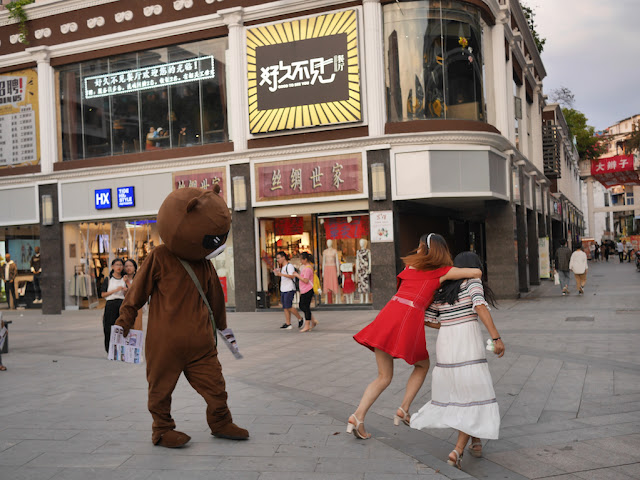 young woman jumping away from a person in a bear suit in Ganzhou