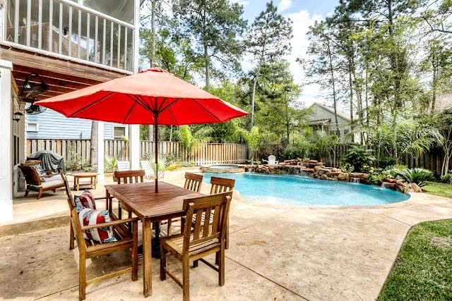 outdoor area with pool and dining table with red umbrella