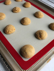 warm peanut butter cookies on baking tray, fresh from the oven and waiting for their chocolate kisses