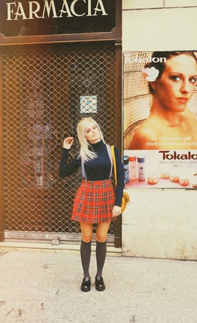 Alejandra Colomera vestida con jersey azul, falda roja cuadros escoceses, tirantes en color gris, calcetas gris y zapatos estilo colegial negro frente a una farmacia antigua